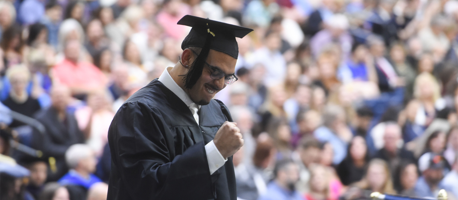 A Belmont graduate celebrates while crossing the stage at commencement.