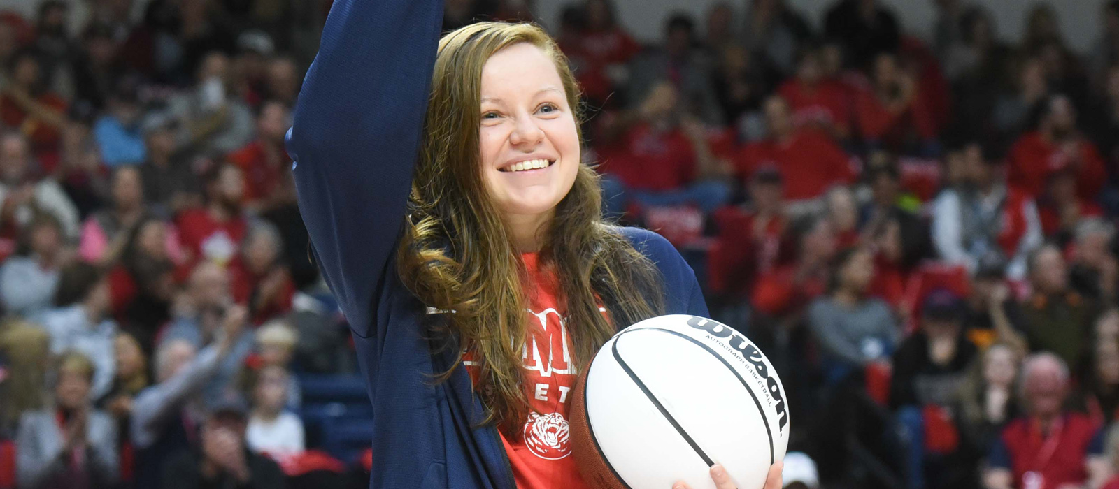 A photo of Darby Maggard holding a basketball and waving to fans.