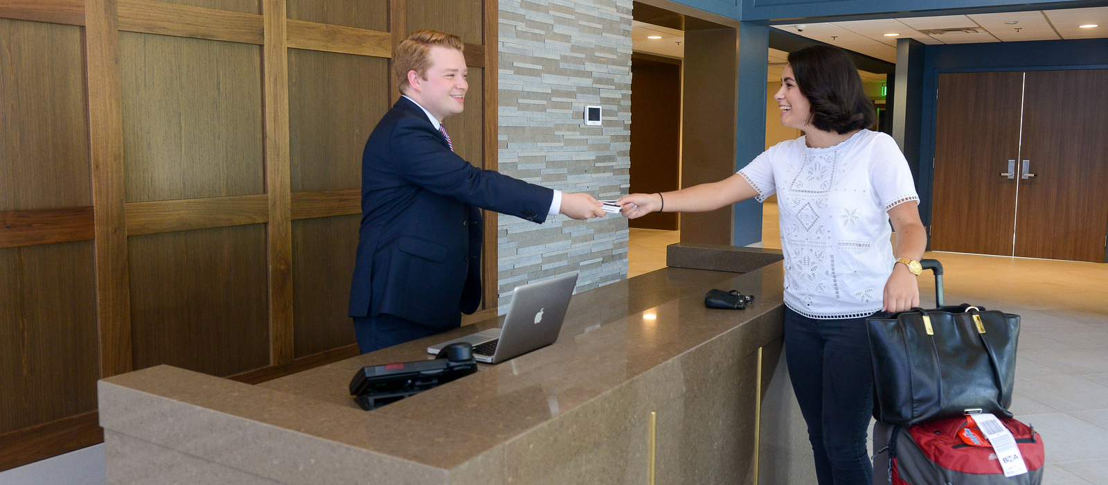 Two students shake hands in a hotel setting.