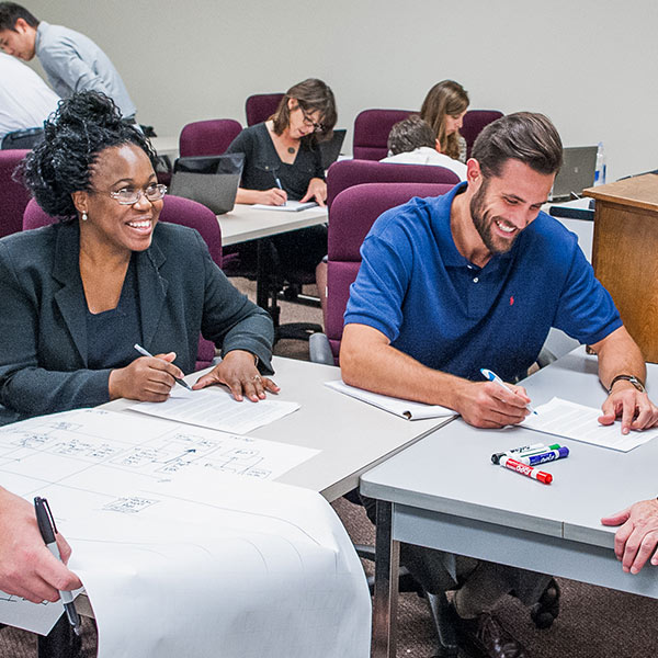 Two business students smiling while taking notes