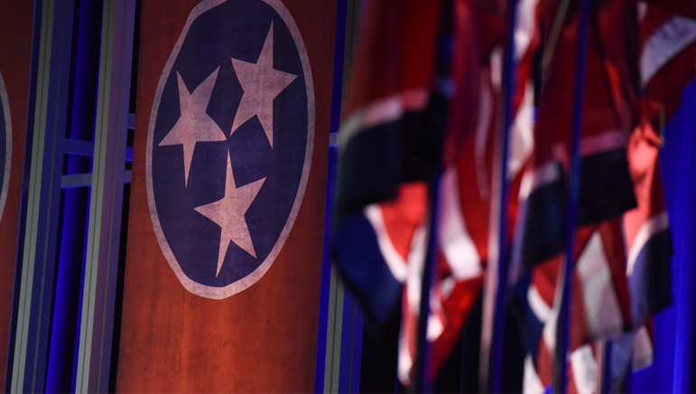 A photo of a Tennessee state flag with other flags in foreground out of focus.