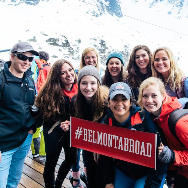 Seven students wearing coats and a hats holding a sign that says #BelmontAbroad on a trip to snowy mountains