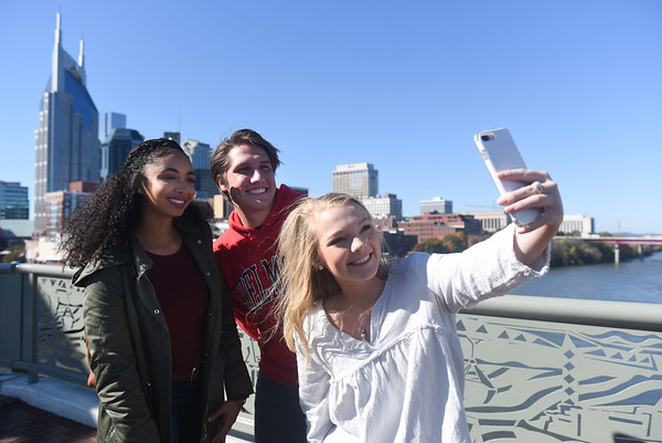 Students take a selfie on a bridge downtown, with the skyline on the horizon.
