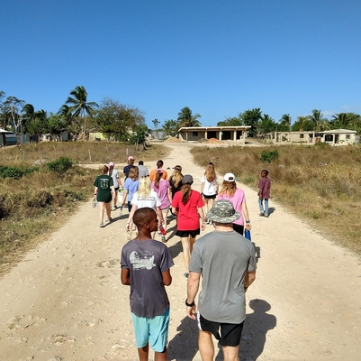 Students walking down gravel road with locals